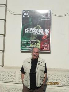 Il Maestro Burli posando con un poster dell'evento alle sue spalle.